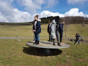 mehrere Personen balancieren auf einer runden Holzscheibe, die nur in der Mitte aufliegt und sich zur Seite neigen kann